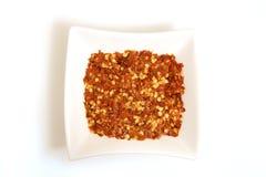 Pepe di peperoncino rosso schiacciato in ciotola bianca quadrata Fotografie Stock Libere da Diritti