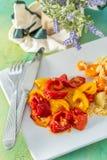 Pepe giallo rosso al forno e riso bianco cucinato con le carote deliziose su un piatto e una forcella e un coltello ceramici bian immagini stock