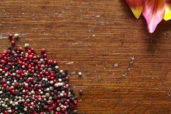 Pepe piccante e bei fiori variopinti sulla tavola di legno scura Immagini Stock Libere da Diritti