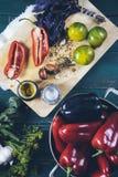 Pepe rosso e nero in ciotola del metallo su fondo di legno e sui pomodori gialli con basilico e spezie su un punto di vista super immagine stock libera da diritti