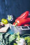 Pepe rosso e nero in ciotola del metallo su fondo di legno e sui pomodori gialli con basilico e spezie su un tagliere, un sano fotografia stock libera da diritti