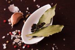 Peper in een kleine witte plaat en baaibladeren Hoogste mening Stock Afbeelding