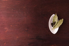 Peper in een kleine witte plaat en baaibladeren Hoogste mening Stock Fotografie