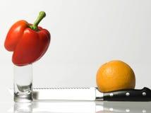 Peper, naranja, cuchillo y vidrio Imágenes de archivo libres de regalías