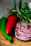 Peper salami and rosemary on cutting board Royalty Free Stock Images