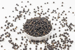 Pepercorn. A bowl with Black pepper on a white background Royalty Free Stock Photos