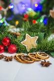 Peperkoek in de vorm van sterren, rode Kerstmisballen, droge citroenen, kaneel en groene slinger en lichten Royalty-vrije Stock Foto's