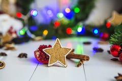 Peperkoek in de vorm van sterren, rode Kerstmisballen, droge citroenen, kaneel en groene slinger en lichten Stock Foto's