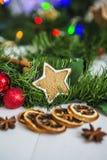 Peperkoek in de vorm van sterren, rode Kerstmisballen, droge citroenen, kaneel en groene slinger en lichten Royalty-vrije Stock Afbeeldingen