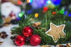 Peperkoek in de vorm van sterren, rode Kerstmisballen, droge citroenen, kaneel en groene slinger en lichten Royalty-vrije Stock Afbeelding
