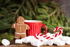 Peperkoekmens dichtbij grote rode kop en Kerstboom, Kerstmisriet en heemst Royalty-vrije Stock Foto's