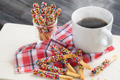 Pepero godis med varmt kaffe på träbakgrund Fotografering för Bildbyråer