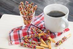 Pepero-Süßigkeit mit heißem Kaffee auf hölzernem Hintergrund Stockbild