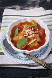 Peperonata. Pepper stew in white bowl with wooden spoon Stock Image
