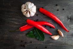 Peperoncini, aglio, foglia di alloro e spezie rossi su fondo di legno nero Immagini Stock