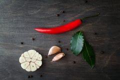 Peperoncini, aglio, foglia di alloro e spezie rossi su fondo di legno nero Immagini Stock Libere da Diritti