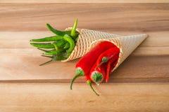 Peperoncini caldi rossi e verdi nei coni del wafer Immagini Stock