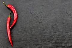 Peperoncini e granelli di pepe roventi su fondo nero, v superiore Fotografia Stock Libera da Diritti