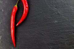 Peperoncini e granelli di pepe roventi su fondo nero, v superiore Fotografie Stock