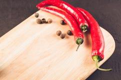 Peperoncini e spezie sui peperoncini roventi vuoti di una commissione di taglio e spezie roventi su un tagliere vuoto Copi lo spa fotografia stock