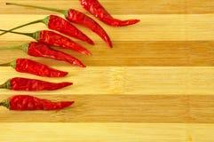 Peperoncini rossi caldi sul bordo di legno Fotografia Stock