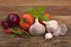 Peperoncini rossi della cipolla rossa del pomodoro dell'aglio e foglie del basilico Immagine Stock