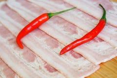 Peperoncini rossi e pezzi deliziosi di bugia del bacon della carne di maiale su una superficie di legno naturale Luce del giorno immagine stock libera da diritti