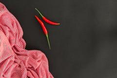 Peperoncini rossi ed asciugamano a strisce Fotografia Stock Libera da Diritti