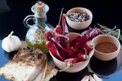 Peperoncini rossi, petrolio, pane, aglio e pepe rossi Fotografie Stock Libere da Diritti