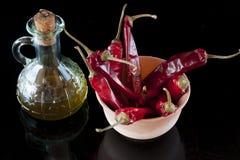 Peperoncini rossi, petrolio, pane, aglio e pepe rossi Fotografie Stock