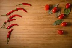 Peperoncini rossi Pomodori e foglia di alloro sul bordo di legno fatto di bambù Fotografia Stock