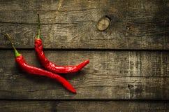 Peperoncini rossi rossi con fondo strutturato Fotografie Stock Libere da Diritti