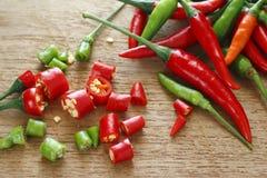 Peperoncini rossi rossi e verdi freschi e peperoncini rossi rossi e verdi freschi tagliati sul blocchetto di spezzettamento di le Immagine Stock