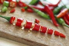 Peperoncini rossi rossi e verdi freschi tagliati sul blocchetto di spezzettamento di legno Fotografie Stock