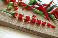 Peperoncini rossi rossi e verdi freschi tagliati sul blocchetto di spezzettamento di legno Fotografia Stock