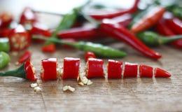 Peperoncini rossi rossi e verdi freschi tagliati sul blocchetto di spezzettamento di legno Fotografie Stock Libere da Diritti
