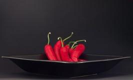 Peperoncini rossi su una zolla Fotografie Stock Libere da Diritti