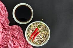 Peperoncini rossi sui germogli della soia, sulla salsa di soia in ciotola e su una st Immagine Stock