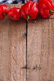 Peperoncini rossi sul bordo di legno Immagini Stock Libere da Diritti
