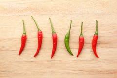 Peperoncini rossi verdi fra i peperoncini rossi rossi Fotografia Stock