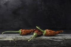 Peperoncini secchi su legno contro una terra scura Fotografia Stock