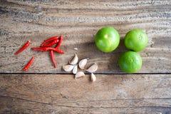 Peperoncino rosso, aglio e calce sulla tavola di legno, erba e piccante asiatici Immagini Stock Libere da Diritti