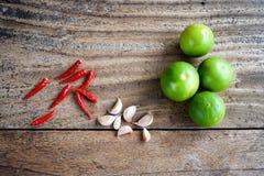 Peperoncino rosso, aglio e calce sulla tavola di legno, erba e piccante asiatici Fotografia Stock