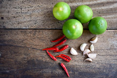 Peperoncino rosso, aglio e calce sulla tavola di legno, erba e piccante asiatici Fotografie Stock Libere da Diritti