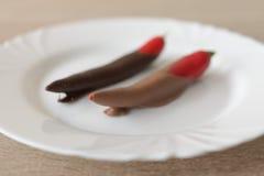Peperoncino rosso in cioccolato marrone sul piatto bianco Fotografia Stock