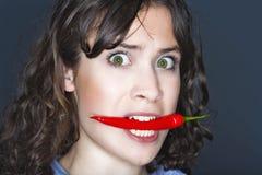 Peperoncino rosso della holding della donna nella sua bocca Immagini Stock Libere da Diritti