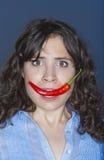 Peperoncino rosso della holding della donna nella sua bocca Immagini Stock