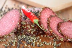 Peperoncino rosso e fette di salame Fotografia Stock