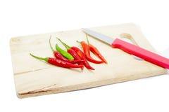Peperoncino rosso rosso con il coltello sul tagliere di legno fotografie stock