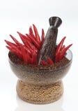 Peperoncino rosso rovente in un mortaio di legno fotografia stock